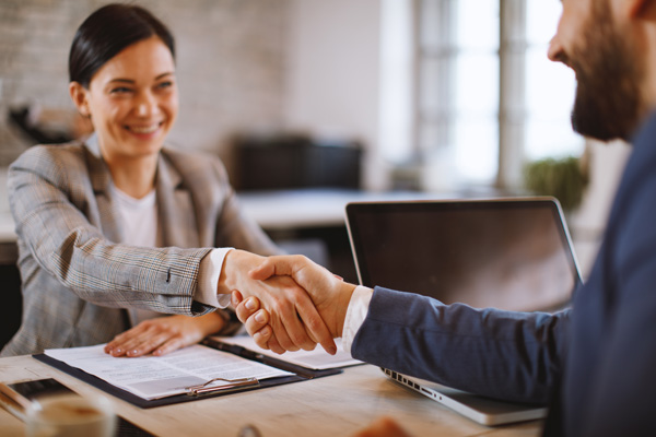 Friendly, smiling business woman shaking hands with client