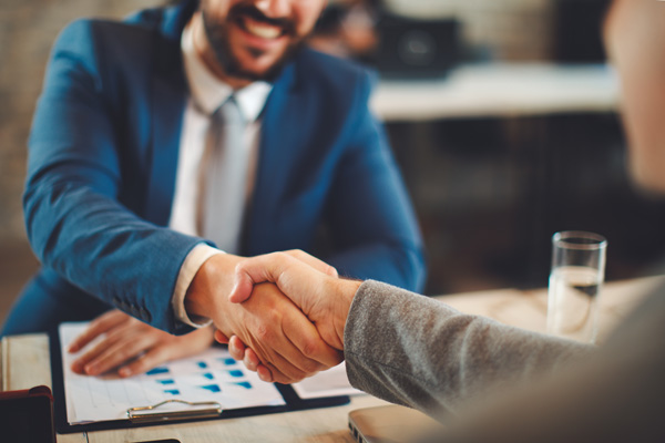 Bearded adult site broker shaking hands with client