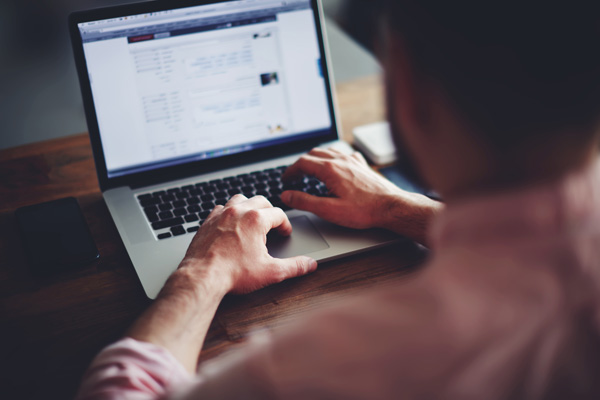 Man scrolling through paysite listings on laptop
