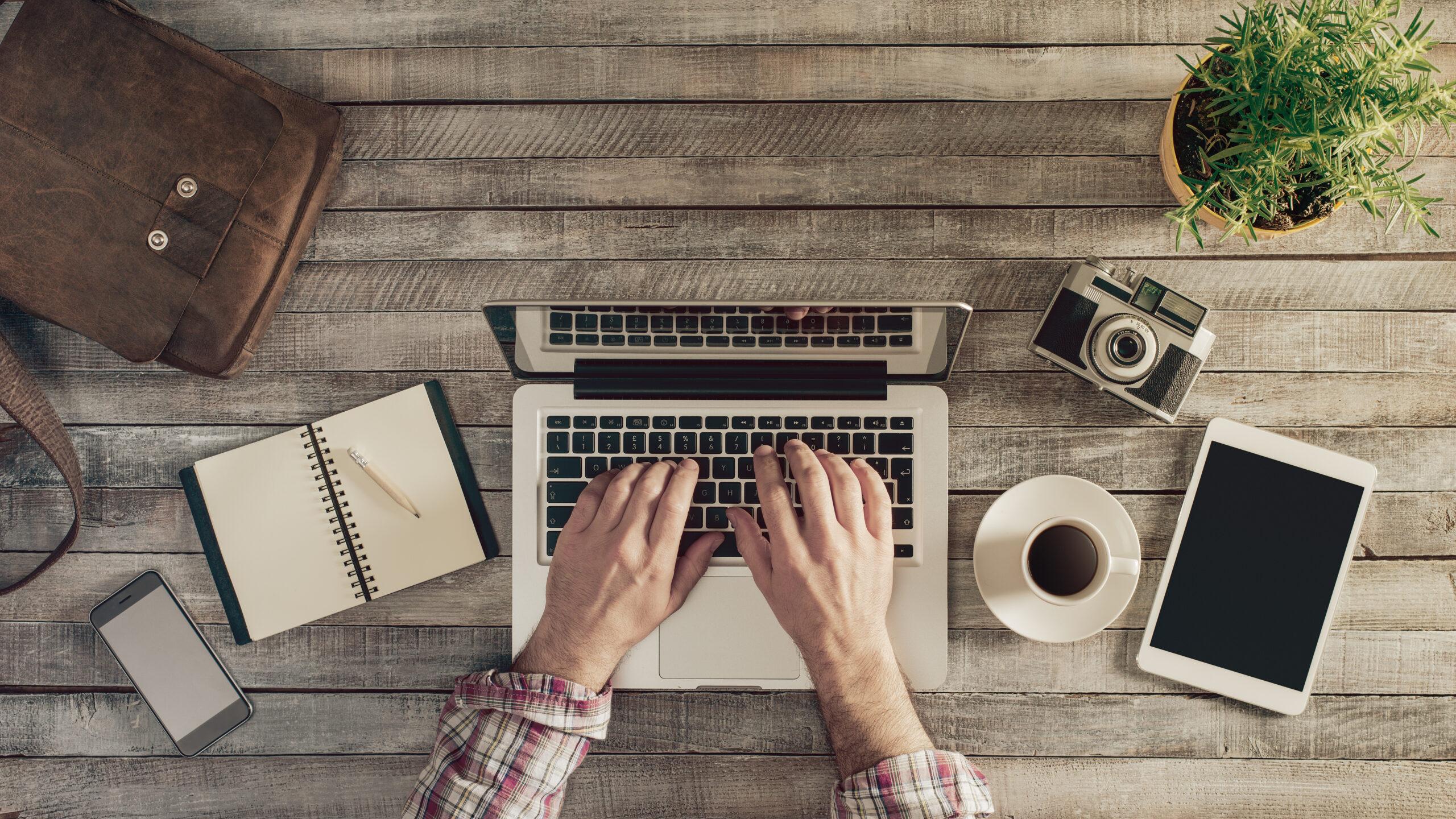 Man using laptop on rustic desktop