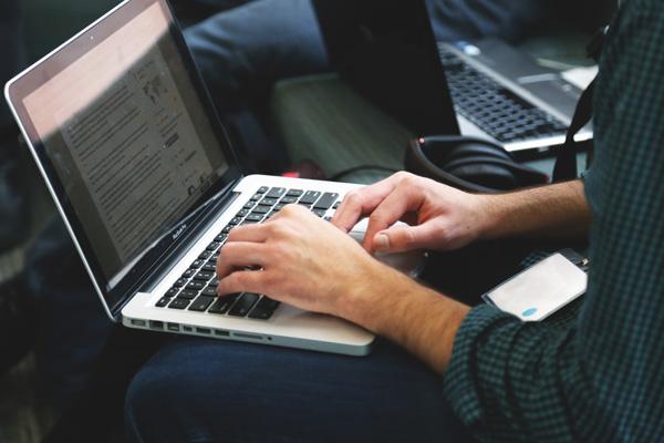 Man browsing membership sites on laptop