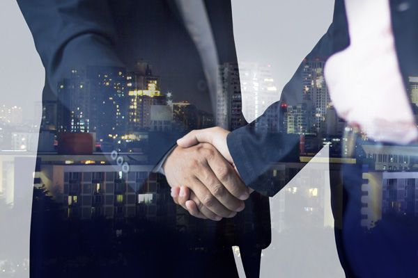 Reflection of adult industry professionals shaking hands in window