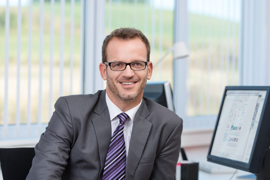 Smiling professional adult site broker in grey suit and glasses