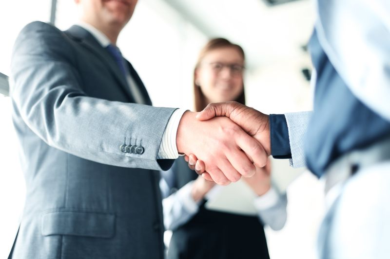 Adult site owner shaking hands with adult site broker after successful sale