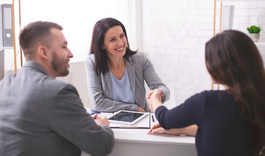 Young couple shaking hands with smiling Adult Site Broker in professional office