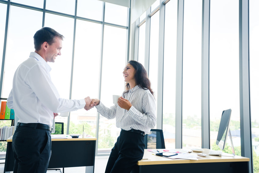 Laughing woman shaking hands with adult site broker in well-lit office