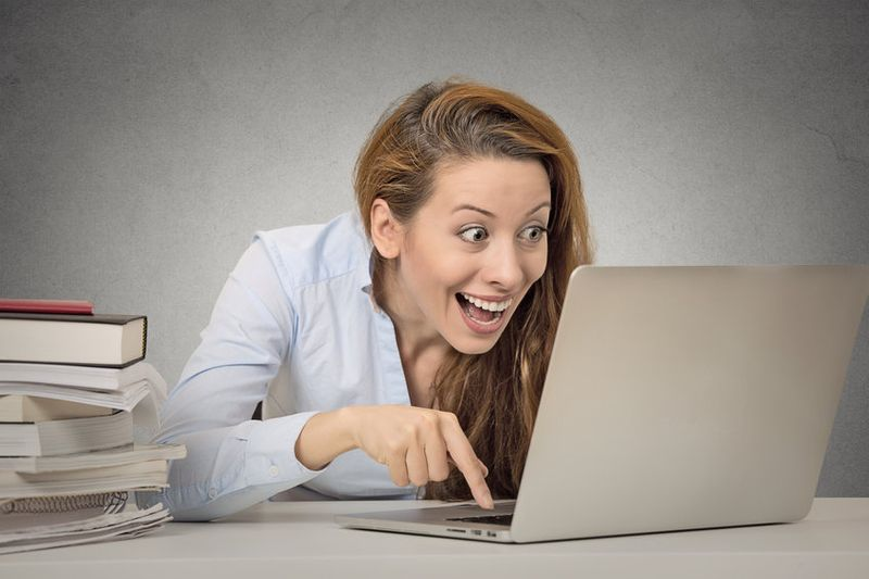 Excited woman exploring dating site on laptop
