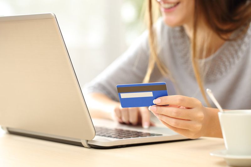 Smiling woman searching for cam sites while holding credit card