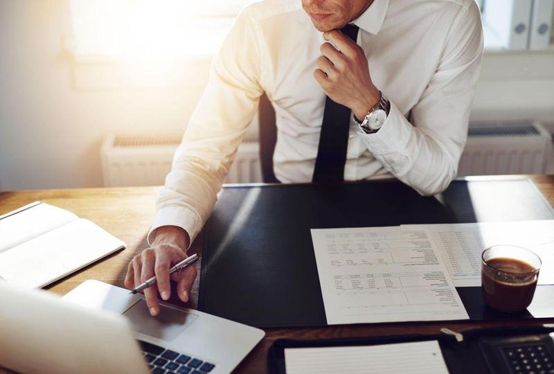Pensive adult site broker exploring adult dating sites at desk
