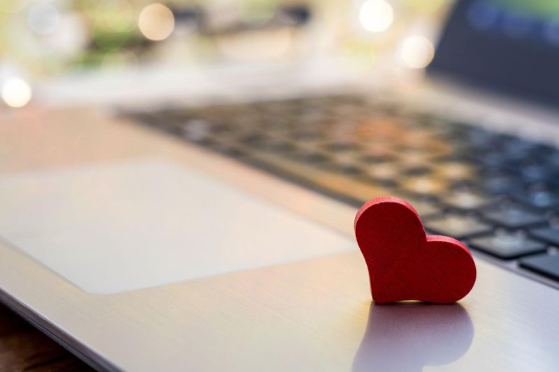 Small wooden heart resting on laptop open to online dating site